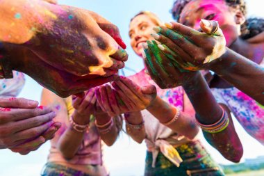 Close-up partial view of young multiethnic friends holding colorful paint in hands at holi festival stock vector