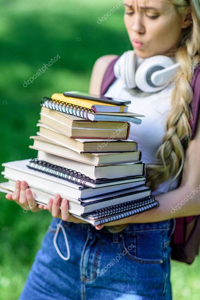 girl holding pile of books