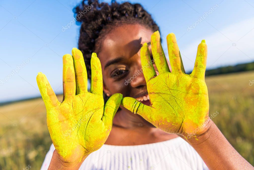 girl with yellow paint on palms