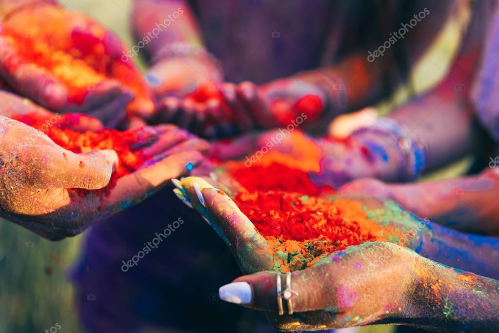 people holding colorful paint