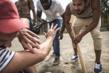 men attacking other one with baseball bats