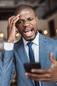 Fotografie angry businessman using smartphone