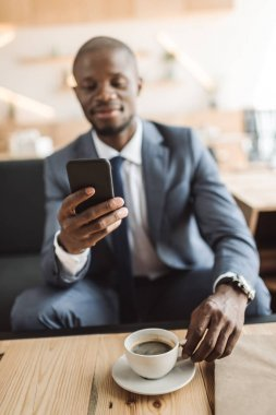 Businessman using smartphone in cafe