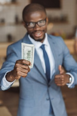 Businessman with money and thumb up