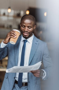 Businessman with coffee reading newspaper