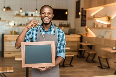 Smiling male african american owner of coffee shop holding little empty blackboard in wooden frame stock vector