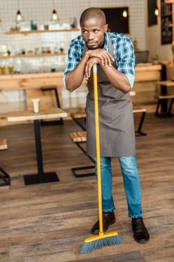 man brooming in coffee shop