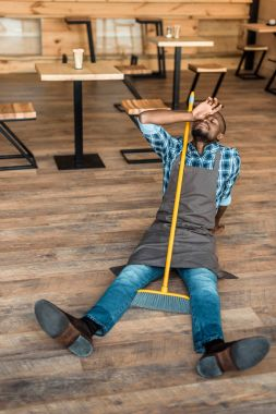 tired man on floor with broom