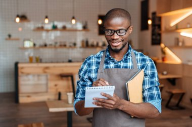Handsome smiling african american waiter taking order with notepad and digital tablet in coffee shop stock vector