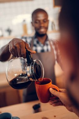 barista pouring coffee on bar