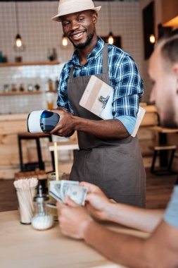 Smiling african american waiter taking cash payment in cafe stock vector