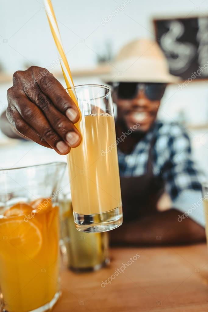 bartender holding glass of lemonade