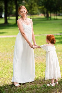 Mother and daughter holding hands at park