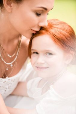 Close-up portrait of beautiful young mother kissing adorable red haired daughter stock vector