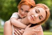 Fotografie matka a dcera objímat v parku