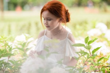 Redhead girl in flower bed