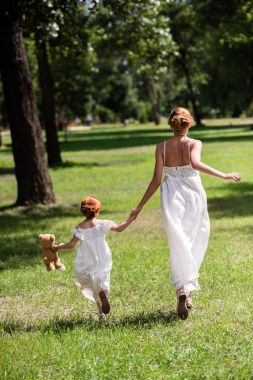 mother and daughter walking at park