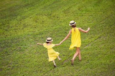mother and daughter walking on lawn