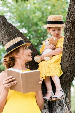 mother and daughter reading in park