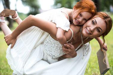 mother piggybacking daughter in park
