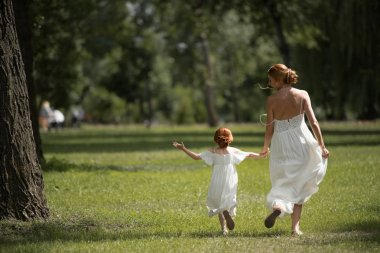 Mother and daughter walking in park