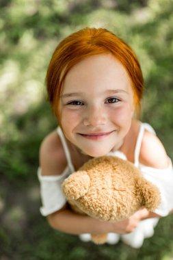 redhead girl with teddy bear