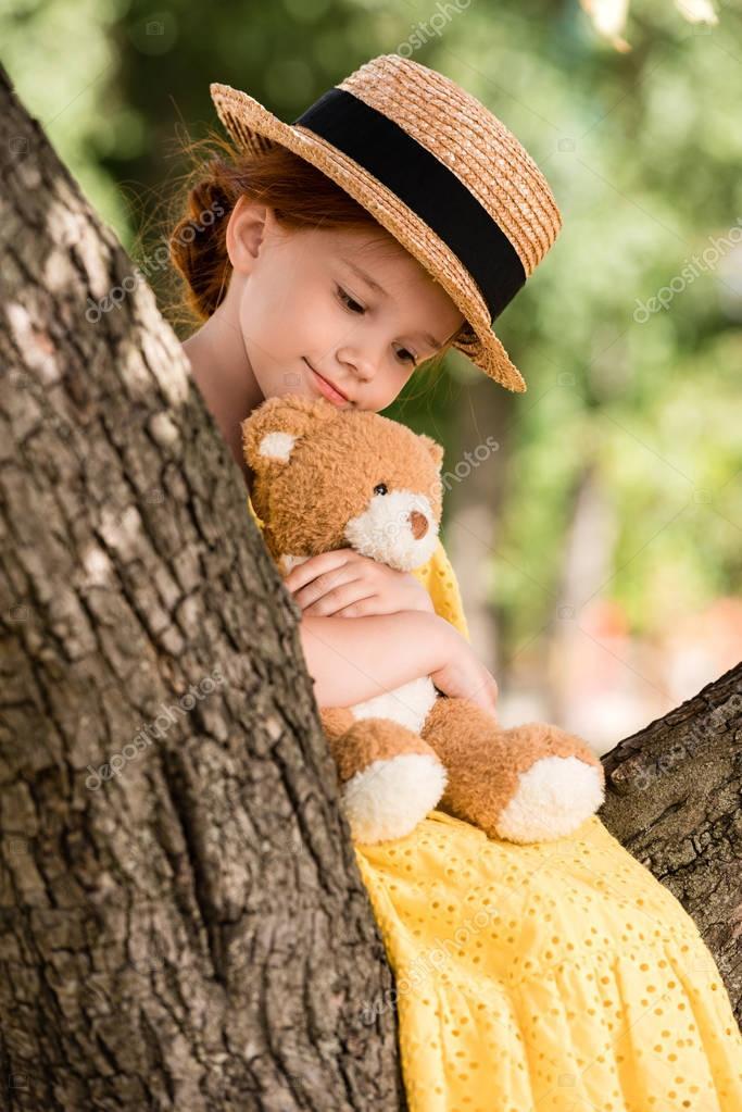 Girl with teddy bear on tree