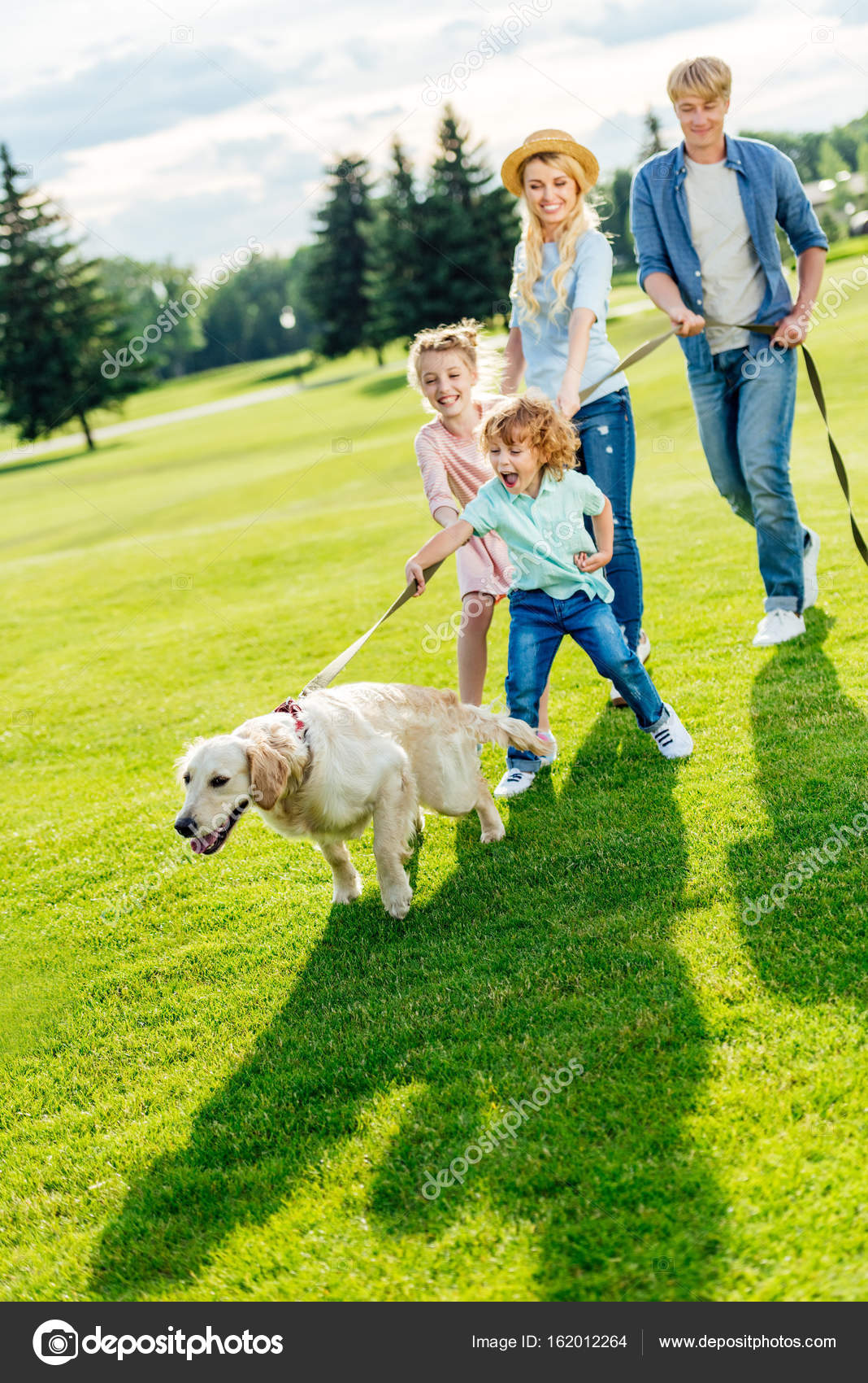 Family With Dog Walking At Park Stock Photo 162012264