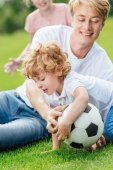 otec a syn hraje fotbal v parku