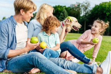 family eating apples at picnic