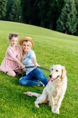 mother and daughter with dog in park