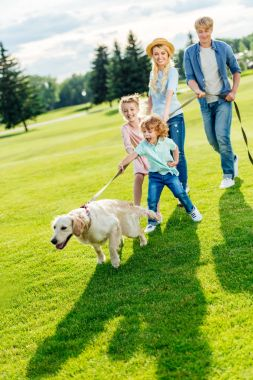 Family with dog walking at park