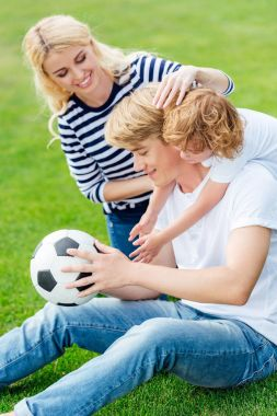 Family with soccer ball playing in park