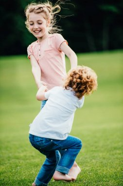 Siblings having fun in park