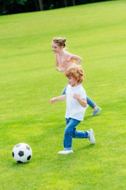 siblings playing soccer in park