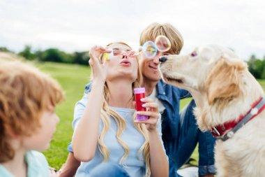 parents with kid blowing soap bubbles
