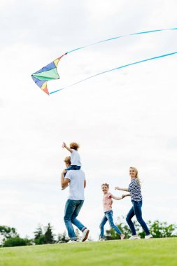 family playing with kite at park