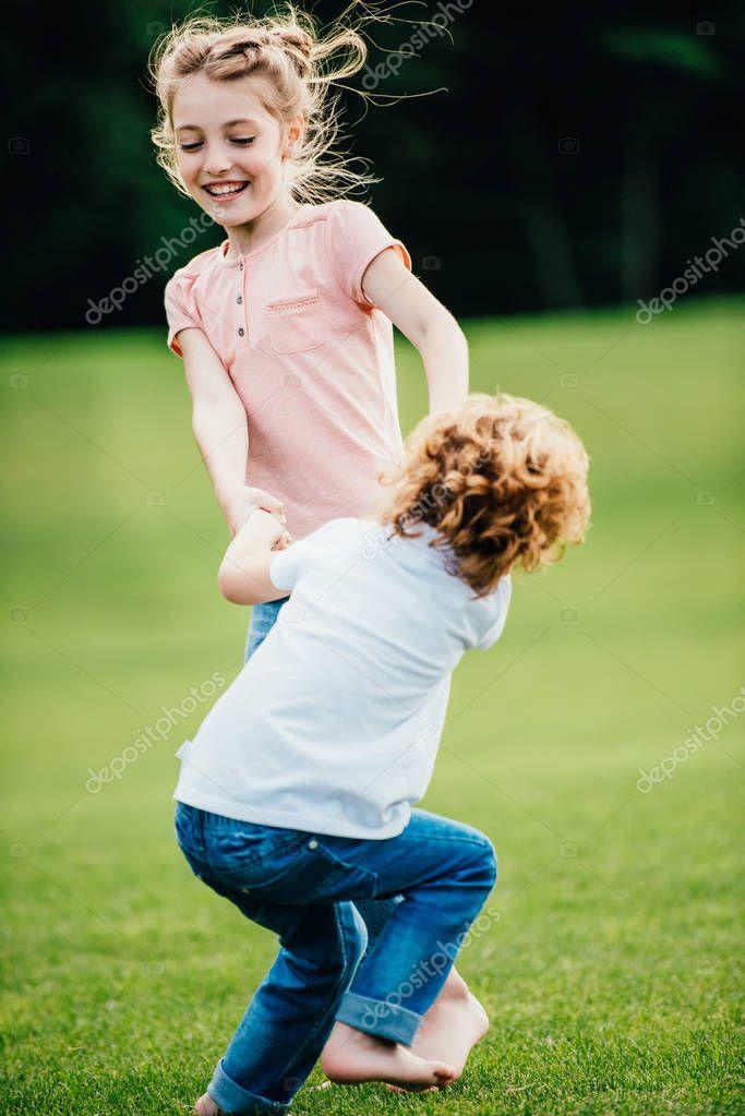 Siblings having fun in park