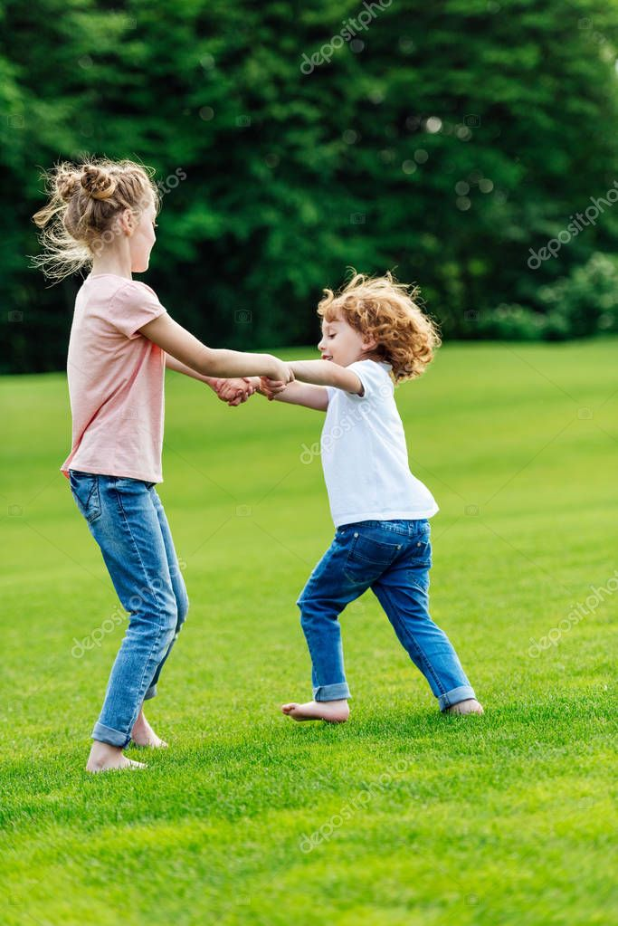 Siblings holding hands in park