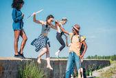 Fotografie Multiethnische Freunde springen von Brüstung