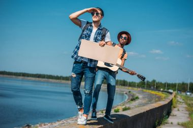 multicultural men with cardboard hitchhiking
