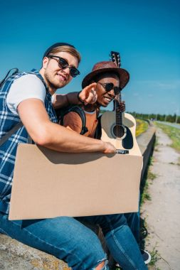 multicultural hitchhikers with cardboard