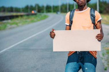 african american hitchhiker with empty cardboard