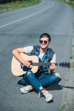 Young smiling man sitting on road and playing guitar stock vector