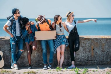 Multiethnic friends pointing away while hitchhiking