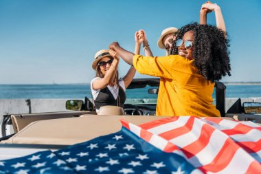 Multiethnic women in car with american flag