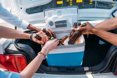 people taking bottles from portable fridge