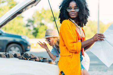 Multiethnic women standing near broken car