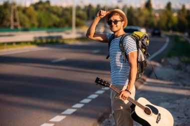 man with guitar hitchhiking alone