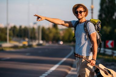 young man with guitar hitchhiking alone